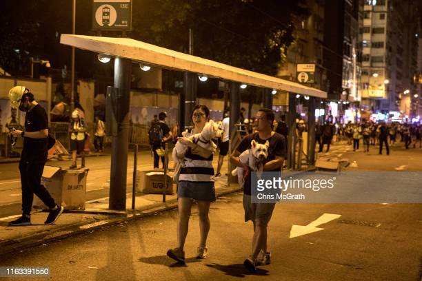 People carry their dogs on a street as protesters clash with police after taking part in an antiextradition bill march on July 21 2019 in Hong Kong...