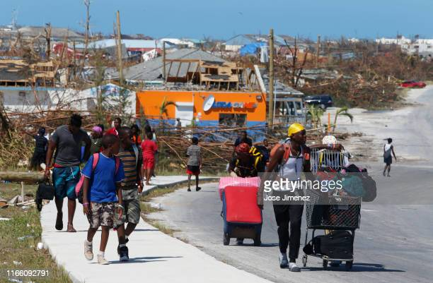 People carry their possessions after Hurricane Dorian passed through in The Mudd area of Marsh Harbour on September 5, 2019 in Great Abaco Island,...