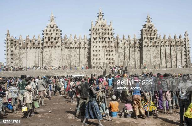 People carry their pots filled with Mud to restore Great Mosque of Djenne in Mali on April 30 2017 The Great Mosque of Djenne listed in UNESCO as a...