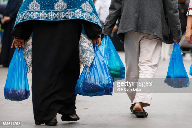 People carry their purchases in plastic carrier bags after shopping at Whitechapel Market in east London on August 17, 2017. British retail sales...