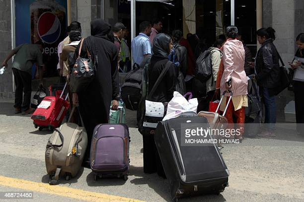 People carry their suitcases as they arrive at Sanaa International Airport on April 6 2015 as hundreds of foreigners are evacuated from conflicthit...