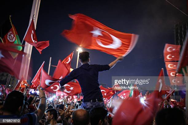 People carry Turkish flags at Taksim Square in Istanbul Turkey on July 17 2016 as they gather to protest the 'Parallel State/Gulenist Terrorist...