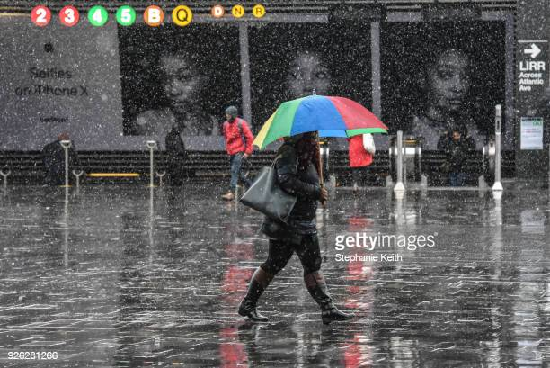 People carry umbrellas during the morning commute during a large storm on March 2 2018 in the Brooklyn borough of New York City A nor'easter is set...