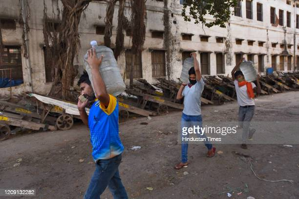 People carry water canisters on day eleven of the 21day nationwide lockdown to curb the spread of coronavirus at Qutab Road on April 4 2020 in New...
