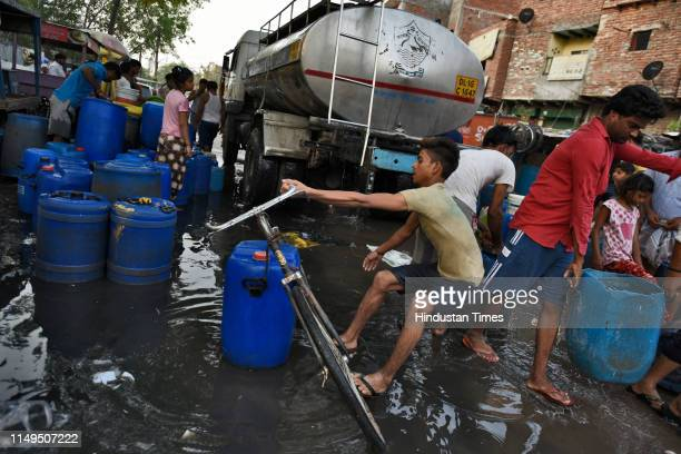 People carry water containers after filling them from a Delhi Jal Board tanker, at Sanjay Colony, Okhla Phase II, on June 12, 2019 in New Delhi,...