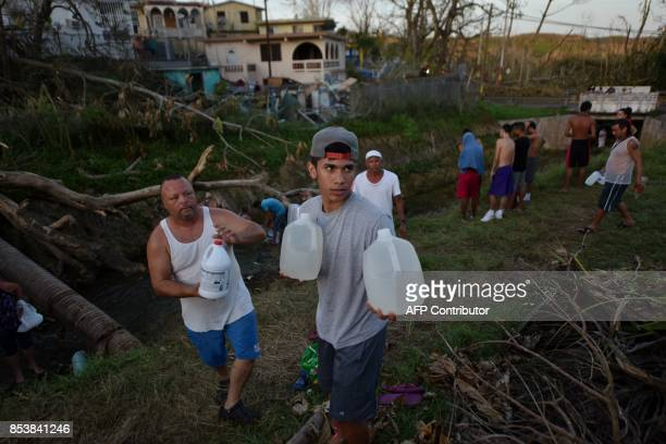 People carry water in bottles retrieved from a canal due to lack of water following passage of Hurricane Maria in Toa Alta Puerto Rico on September...