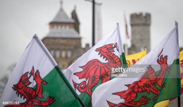 People carry Welsh flags as they attend a parade, one of the largest events being held in Wales to mark St David's Day, on March 1, 2017 in Cardiff,...