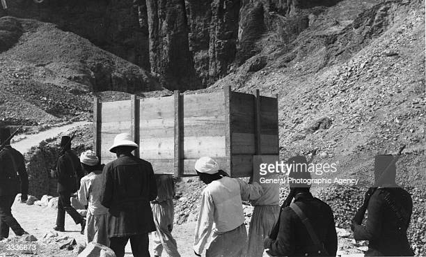 People carrying a crate full of treasures from the tomb of Egyptian pharaoh Tutankhamen at Thebes escorted by armed soldiers
