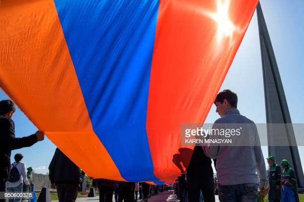 People carrying a giant Armenian flag take part in a ceremony commemorating the 103rd anniversary of the massacre of 15 million of Armenians by...