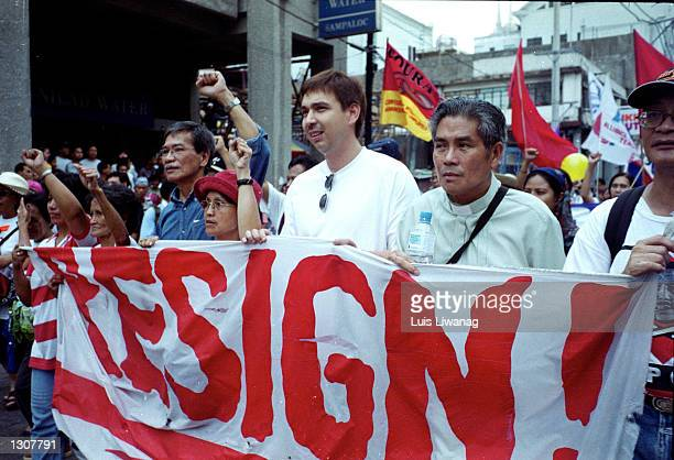People carrying a large banner lead antiEstrada protesters as they block city streets demanding Philippine President Joseph Estrada''s resignation...