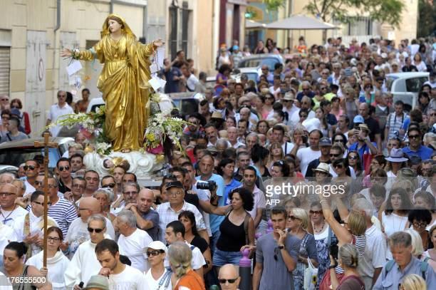 People carrying a statue of the Virgin Mary walk in Marseille's streets southern France on August 15 during a procession celebrating the feast of...