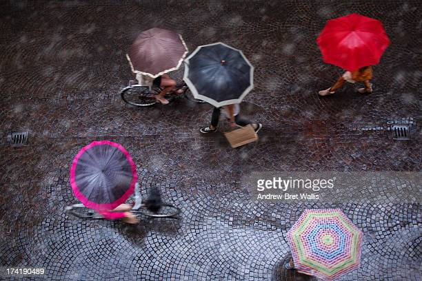People carrying a variety of umbrellas in the rain