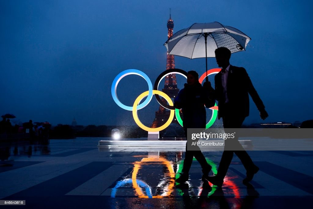 People carrying an umbrella walk past the Olympics Rings on the Trocadero Esplanade near the Eiffel Tower in Paris, on September 13, 2017, after the International Olympic Committee named Paris host city of the 2024 Summer Olympic Games. The International Olympic Committee named Paris and Los Angeles as hosts for the 2024 and 2028 Olympics on September 13, 2017, crowning two cities at the same time in a historic first for the embattled sports body. /