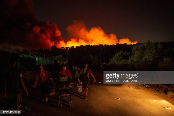 People carrying belongings flee flames after a major fire broke out in the Moria migrants camp on the Greek Aegean island of Lesbos, on September 9,...