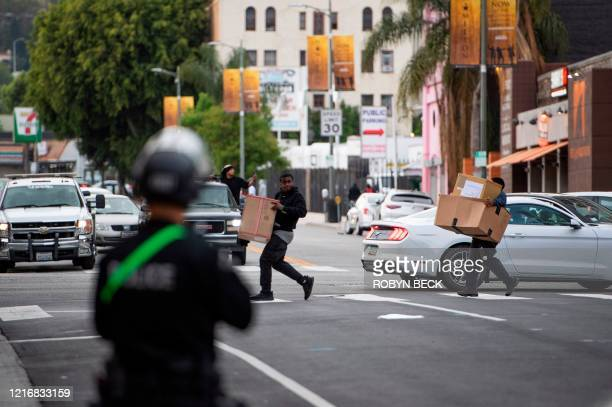 People carrying boxes of goods run past a police line in Hollywood California as peaceful protests and looters broke into stores in Hollywood...