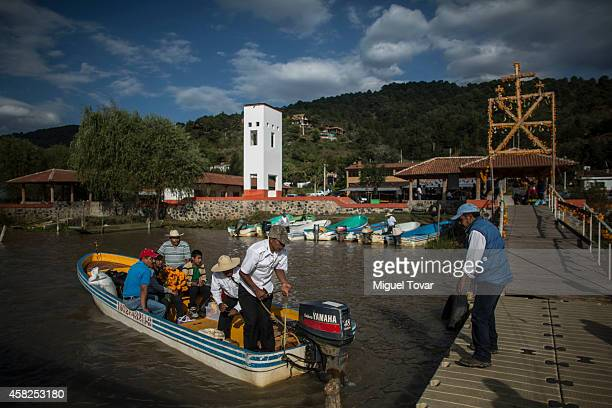 People carrying cempasuchil flowers look for boats to cross the Patzcuaro lake to reach the Janitzio Island one of the most important places to...