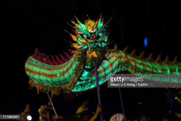 people carrying chinese dragon at night - chinese dragon stock photos and pictures