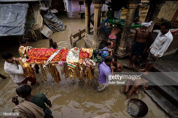 CONTENT] People carrying deadbody through waistdeep water in Monikornika Ghat area on 2nd September 2013 as Ganga is flowing above danger mark in...