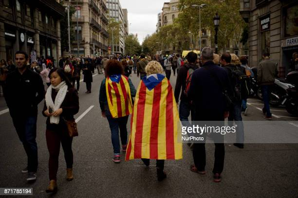 People carrying estelada or proindependence flags walk on the streets of Barcelona Spain on 8 November 2017 Catalonian territory went on general...