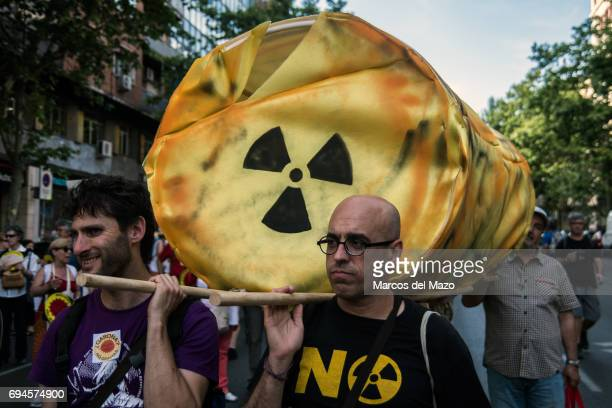 People carrying fictional nuclear waste protesting against nuclear power plants demanding their closure.