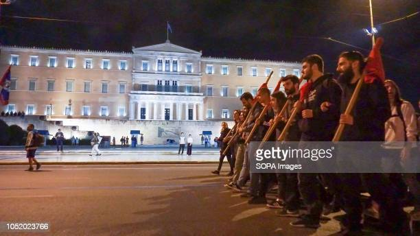 People carrying flags marching towards Hellenic Parliament building during an antiwar rally in Athens Around one hundred protesters took to the...