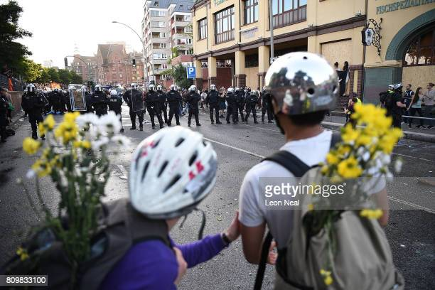 People carrying flowers and wearing cycling helmets look at the riot police during the Welcome to Hell protest march on July 6 2017 in Hamburg...
