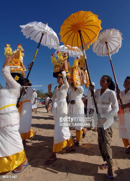 People carrying longpoled umbrellas walk in line during a ritual as part of the celebration of the day of Melasti at Jimbaran on resort island of...