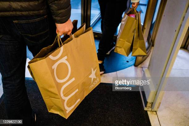People carrying shopping bags exit from the Macy's flagship store in the Herald Square area of New York, U.S., on Friday, Nov. 27, 2020. With sparse...