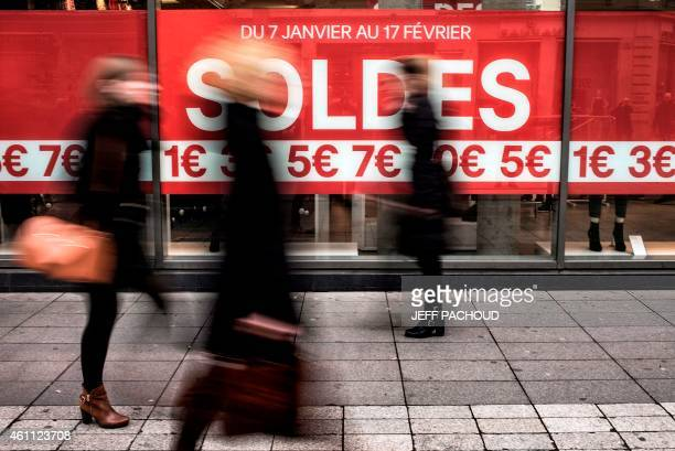 People carrying shopping bags walk past a shop advertising the start of the January sales on January 7 2015 in Lyon on the first day of the winter...