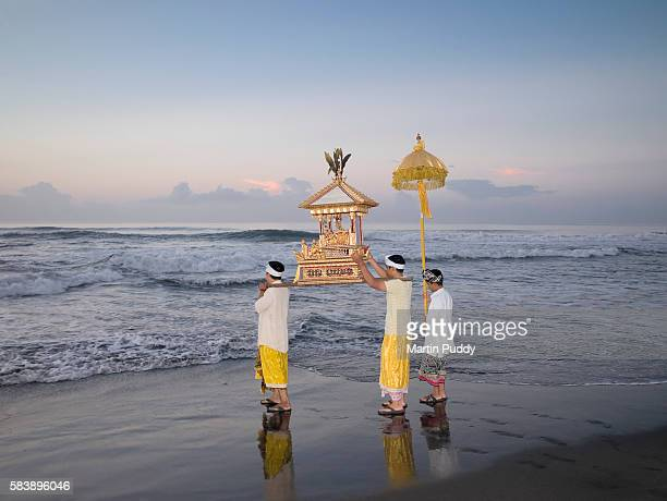 People carrying statues towards the ocean during Melasti Festival