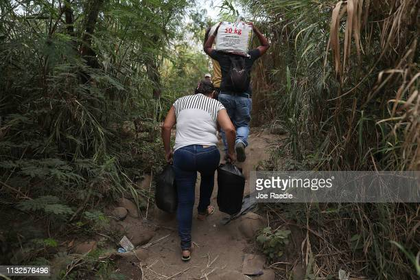 People carrying supplies walk along a trail to cross through the low waters of the Táchira River near the Simón Bolívar international bridge which...