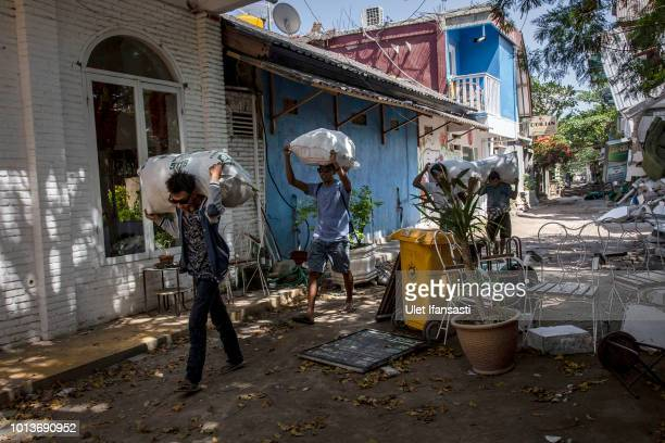 People carrying their belongings at Gili Trawangan island following Sunday's earthquake on August 9 2018 in Lombok Island Indonesia The official...