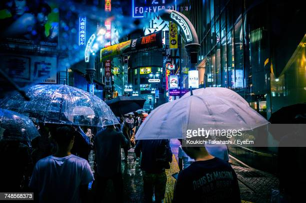 People Carrying Umbrella While Walking On Street During Monsoon At Night