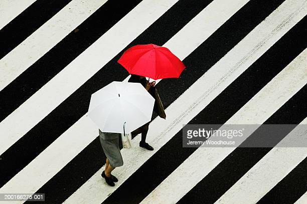 People carrying umbrellas, crossing street at crosswalk, elevated view