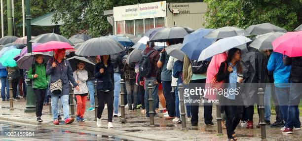 People carrying umbrellas stand in line to register to enter the Reichstag building under pouring rain and temperatures of 16 degreees Celsius in...
