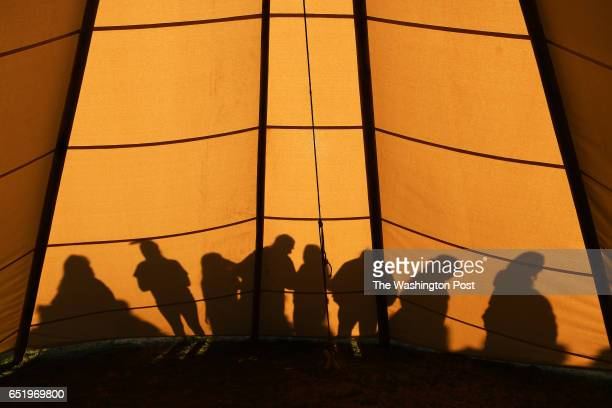 People cast shadows against a teepee near the Washington Monument as people gather leading up to a demonstration against the Dakota Access Pipeline...