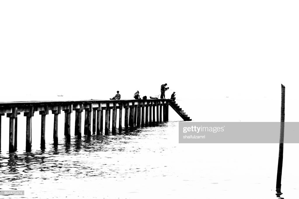 TELUK PELANDUK, MALAYSIA - 24TH DEC 2017; People cast the fishing rod to the sea. Black and white for classic view on old jetty. The old jetty still use for fisherman on fishing activities. : Stock Photo