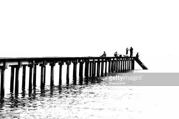 teluk pelanduk, malaysia - 24th dec 2017; people cast the fishing rod to the sea. black and white for classic view on old jetty. the old jetty still use for fisherman on fishing activities. - shaifulzamri fotografías e imágenes de stock
