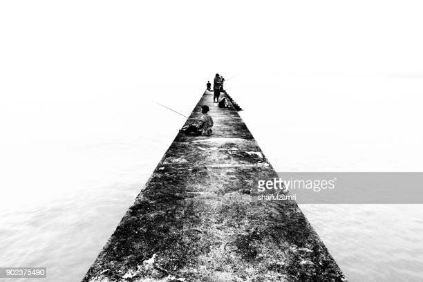 teluk pelanduk, malaysia - 24th dec 2017; people cast the fishing rod to the sea. black and white for classic view on old jetty. the old jetty still use for fisherman on fishing activities. - shaifulzamri photos et images de collection