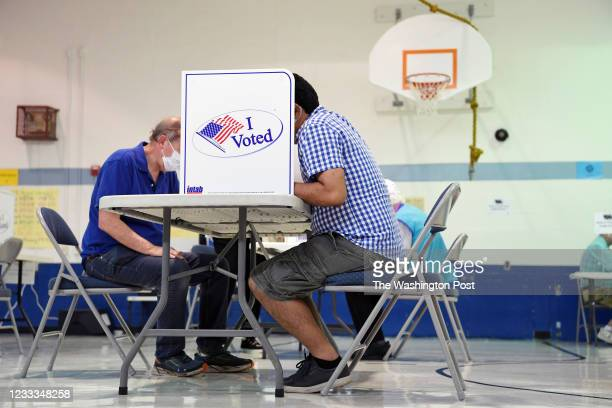 People cast their ballots during primary voting at Lyles-Crouch Traditional Academy on Tuesday June 08, 2021 in Alexandria, VA.
