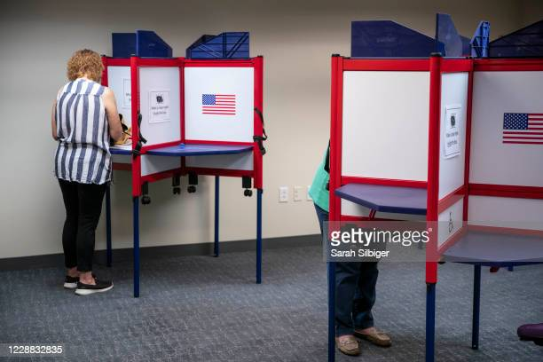 People cast their ballots for the 2020 presidential election at an early voting location on October 1, 2020 in Alexandria, Virginia. Virginia's early...