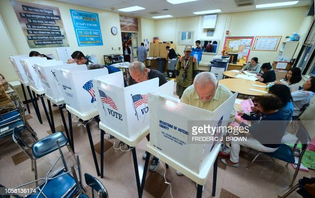 People cast their ballots in voting booths at the 2nd Street Elementary School in the Boyle Heights neighborhood of Los Angeles California on...