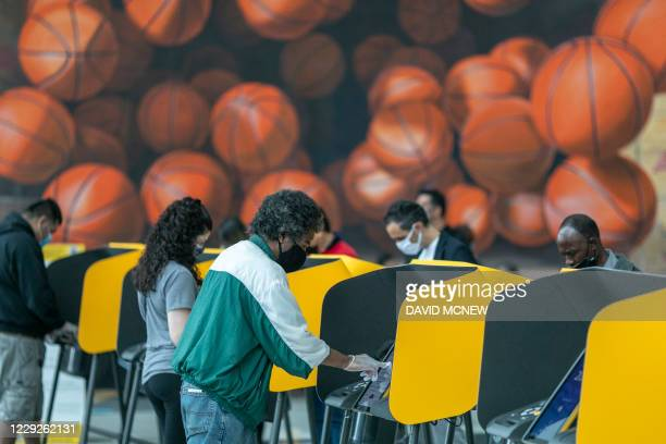 People cast their vote on the first day of early voting at the Vote Center at Staples Center sports and entertainment arena in Los Angeles,...
