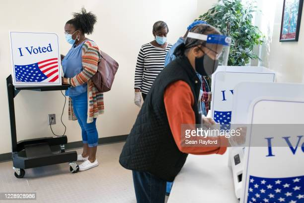 People cast votes at the Richland County Voter Registration & Elections Office on the second day of in-person absentee and early voting on October 6,...