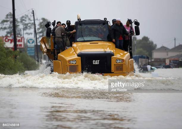 People catch a ride on a construction vehicle down a flooded street as they evacuate their homes after the area was inundated with flooding from...