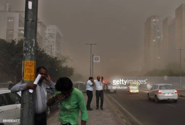 People caught in sudden thunderstorm followed by rain at Connaught Place on May 30 2014 in New Delhi India At least nine people were killed in the...