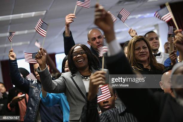 People celebrate after family members took the oath of allegiance to the United States at a naturalization ceremony on January 17 2014 in New York...