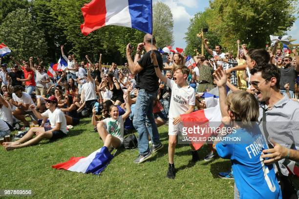 People celebrate after France scored the opening goal as they watch on a giant screen the Russia 2018 World Cup round of 16 football match between...