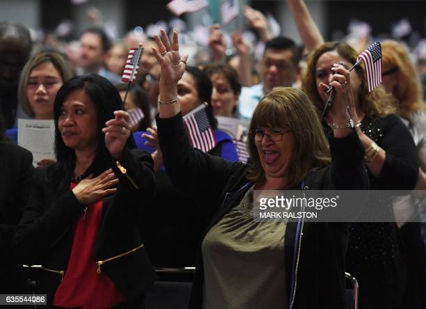People celebrate after pledging allegiance to the United States of America and becoming US citizenship at a naturalisation ceremony for immigrants in...