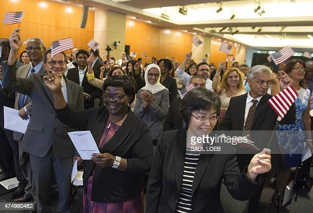People celebrate after taking the citizenship oath to become US citizens during a naturalization ceremony at the US Patent and Trademark Office in...